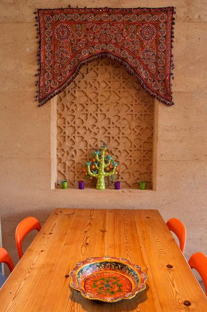 A Dining Table And Wall Niche With Ornamanetic Decorative Element Above It