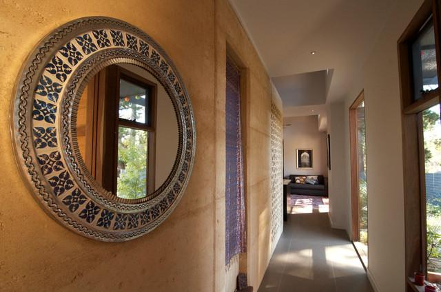 A long hallway with a mirror on the wall and a door to the garden - Sustainable Home Interior Design - an Exciting Review