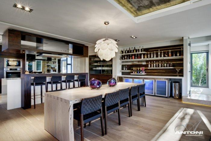 Open kitchen with home bar besides and a dining area in front of them - Contemporary and Luxury House Interior Design in Cape Town