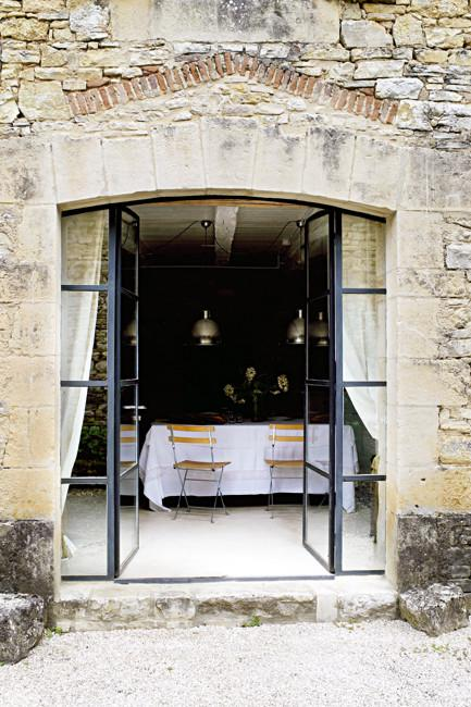Open dining room with doors leading to the outdoor areas - Rustic French Country Home Interior Design in Paris