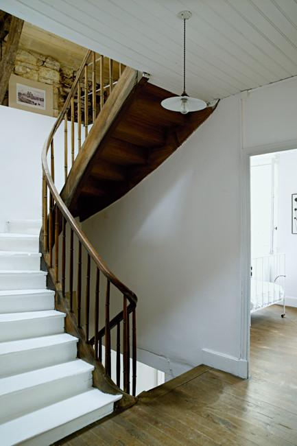White wooden staircase with wooden railings - Rustic French Country Home Interior Design in Paris