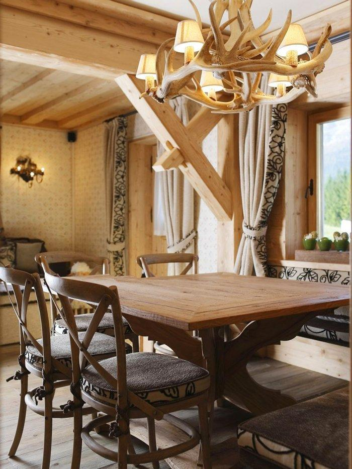 Wooden dining table and antler chandelier in an apartment in a rustic style
