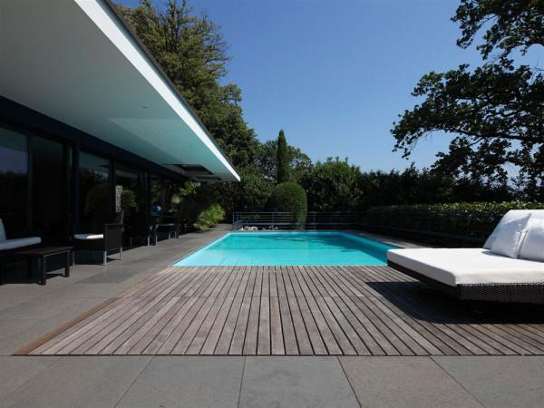 The outdoor swimming pool, placed in a wooden deck - Luxury interior design of a villa by Bruno Klauser