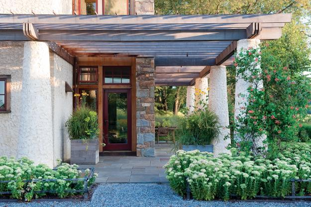 The main entrance of the sustainable house with Beautiful Outdoor Garden Areas