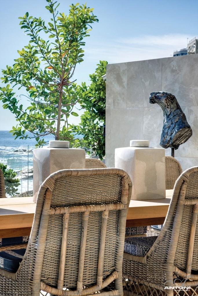 Rattan terrace chairs in a luxury property - Impressive Minimalist Beachfront Apartment by ANTONI ASSOCIATES