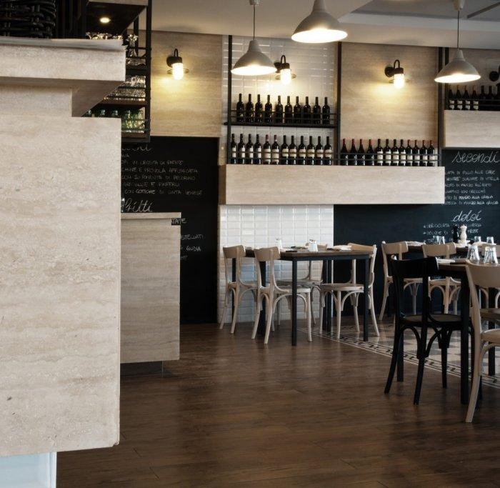 Restaurant tables and wine collection on the wall - La Cucineria