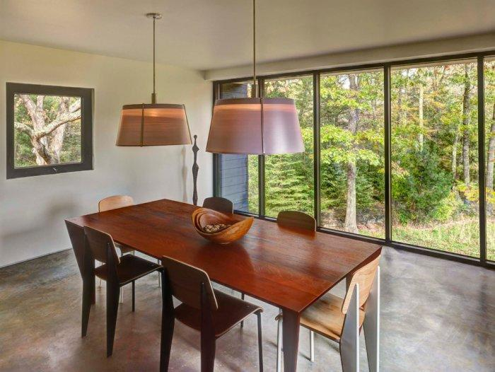 Wooden dinner table in the dining room facing a nive view - The Modern Architecture of a Weekend House by Chan-Li Lin