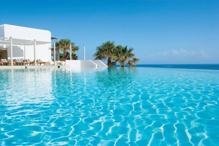 Boundless swimming pool with white lounge areas - The Paradise Seaside Mediterranean Villa in Mykonos, Greece