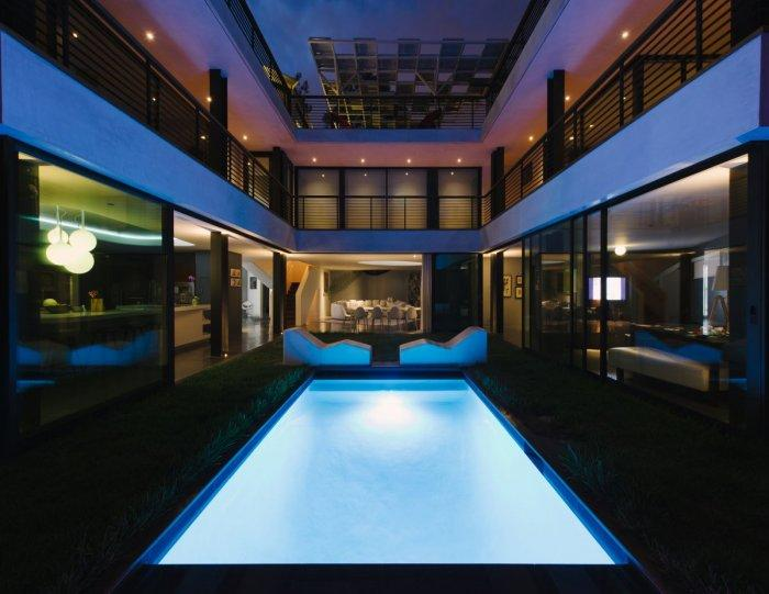 Luxury garden pool at night in a White Two-Storey House in Los Angeles, California