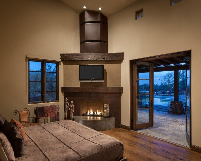 Luxury rustic master bedroom with a stylish fireplace in a Family Desert House in Arizona