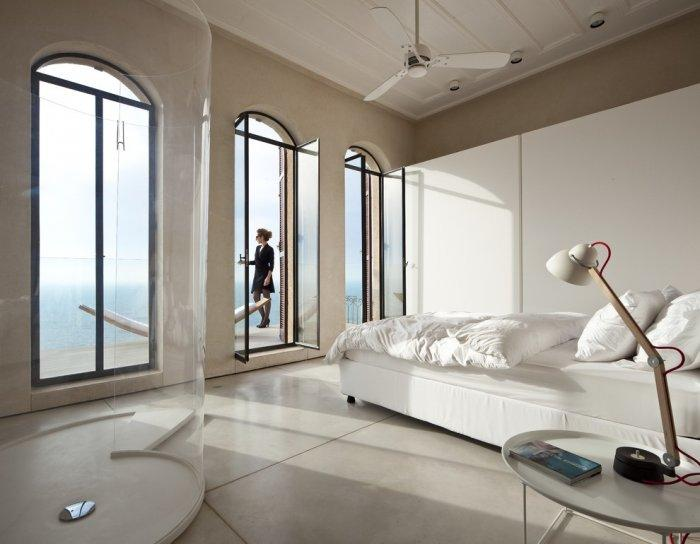 spacious bedroom design wit ha touch of white an transparent shower: Spectacular Ancient Seaside Penthouse in Tel Aviv