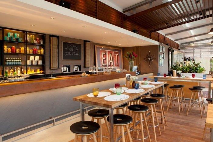 Wooden cafe bar with black leather stools - The Friendly and Cozy Café Melba by Designphase dba