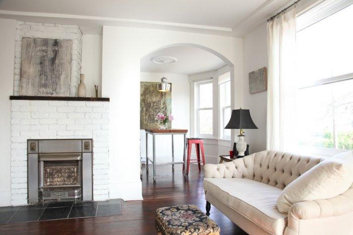Eclectic white living room with gas fireplace - Two eclectic apartments in Vancouver