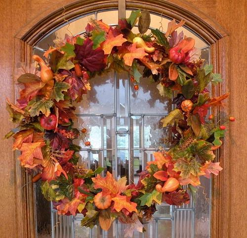 Front door with beautiful fall wreath in orange colors - 9 Easy DIY Decorating Ideas with Autumn Leaves