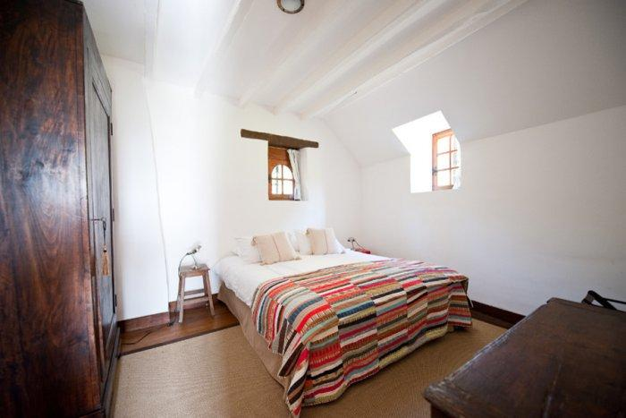 Rustic bedroom interior design with colorful bed setting - La Maisonnette - A Romantic French Cottage