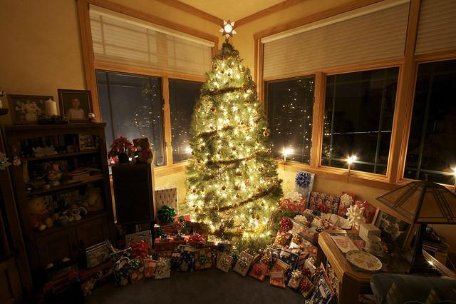 Decorated family Christmas tree full of light and gifts - How to Set the Decoration Properly