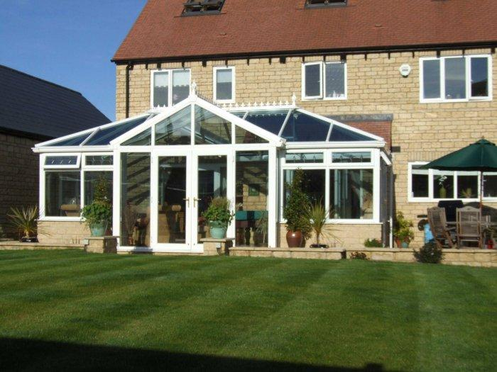 Home conservatory and sunny lawn in front of it - Benefits of your bespoke conservatory