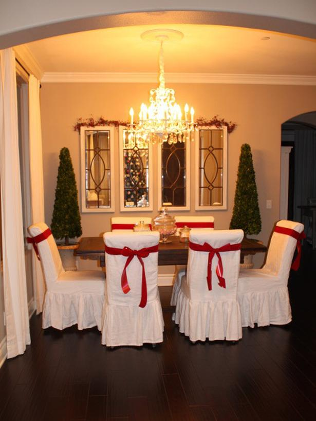 Christmas table with white chairs wrapped in red ribbons - 24 Dazzling Settings for a Sparkling Holiday Night