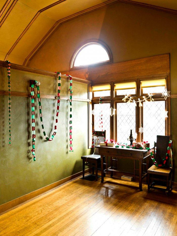 Handmade colorful garlands and paper chains decorate the wall - Christmas Home Decor Ideas and Examples