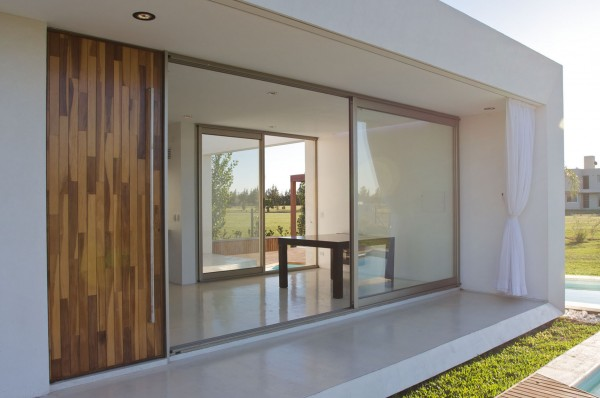 Elegant facade with huge sliding glass doors-Extermely tiny modern home by VismaraCorsi Arquitectos
