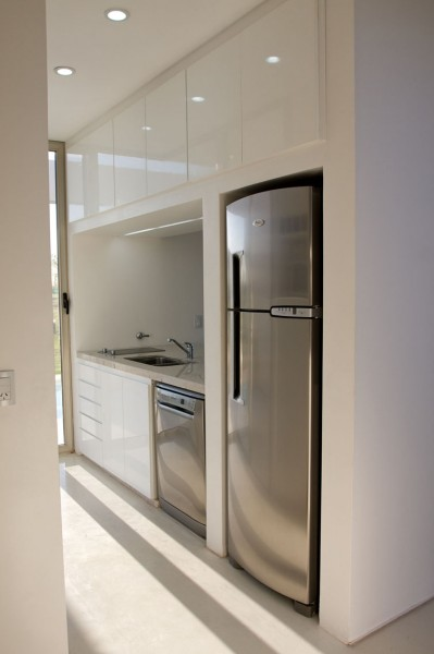 Small minimalist kithen with white glossy surface cabinets-Extermely tiny modern home by VismaraCorsi Arquitectos