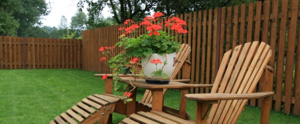 Two garden wooden Adirondack chairs and a vase of flowers between them-Sweet and Interesting Patio and Garden Furniture Ideas