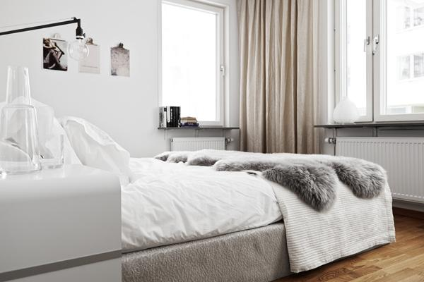 bedroom in white with cozy bedsheets- Minimalist Small Apartment Interior Design