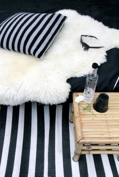 Black and white pillows and rug at a Scandinavian balcony-Trendy designs for outdoor home spaces