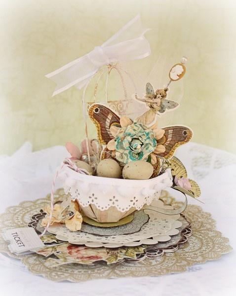 Little fairy and painted eggs in a tea cup