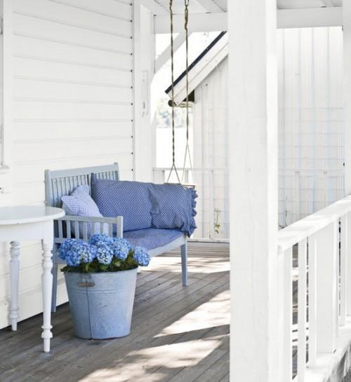 Shabby chic veranda with blue sofa- interior design and home decorating ideas