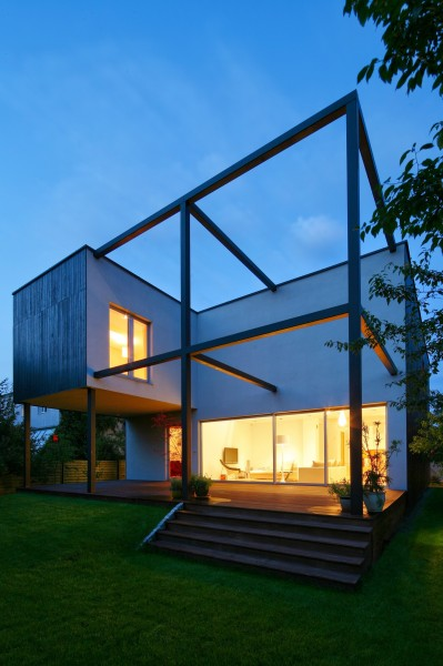 The living room and the wooden deck by night-Contemporary House Architecture and Interior Design in Poland
