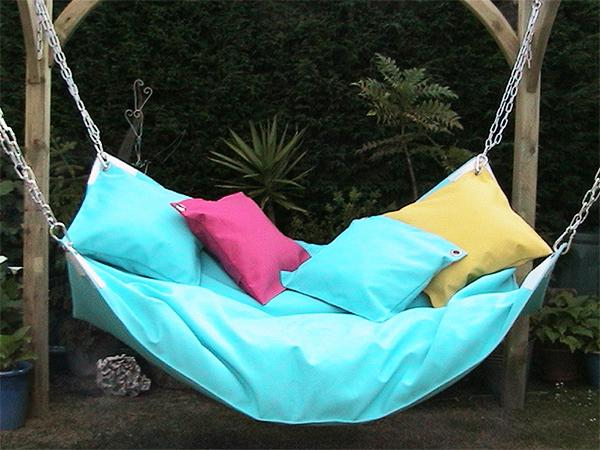 Comfortable relaxing swing with cushions– a home garden lounge zone