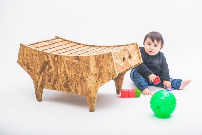 Kid playing next ot a stylish modern stool made of wood