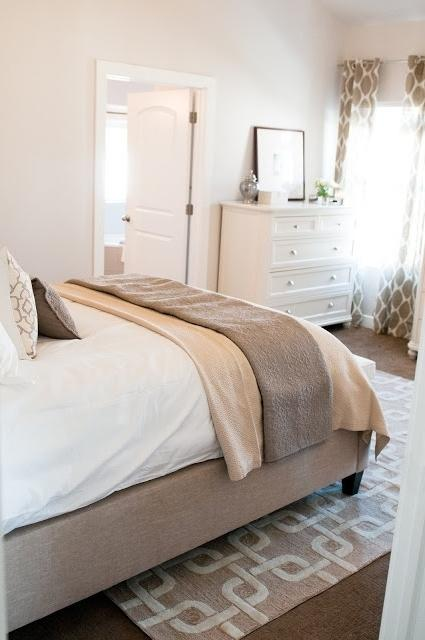 Master bedroom with creme colored walls and bed cover