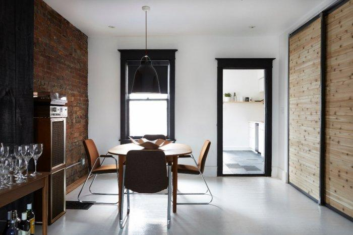 Small dining room with exposed brick wall- inside a small eclectic house