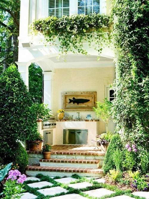 Summer villa - sunny outdoor kitchen with natural crawling plants decorating the facade
