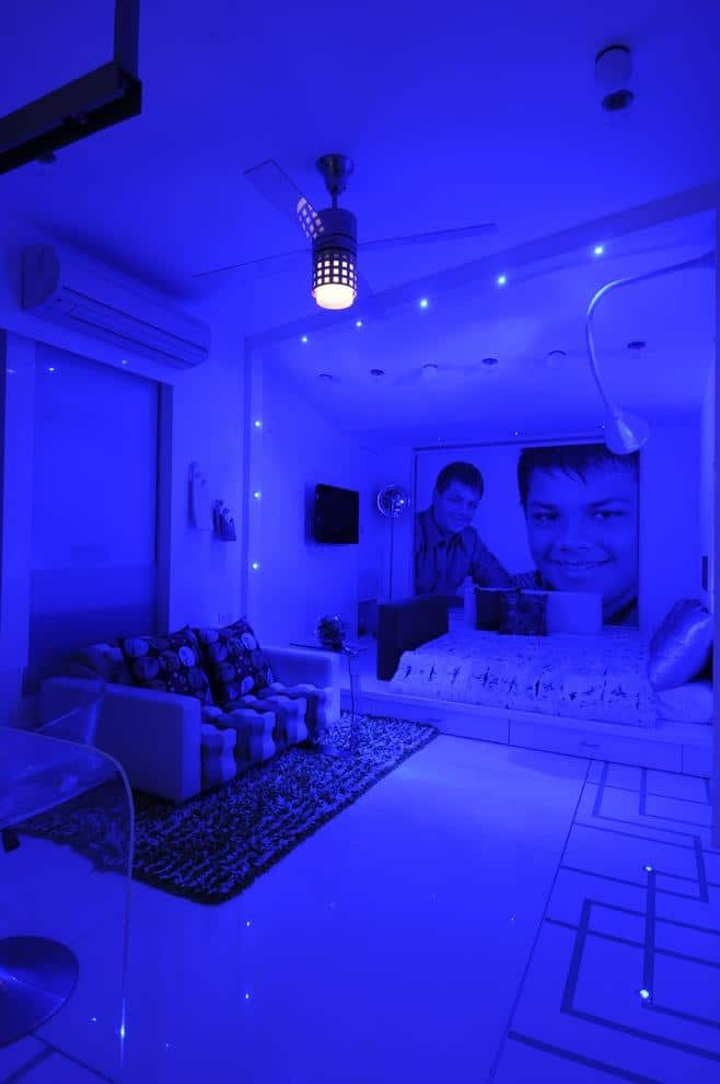 Boy's bedroom illuminated in blue with a portrait of the owner on the wall