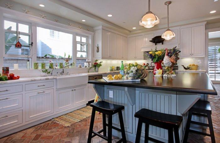 Coastal house interior and its beautiful white kitchen with window in front of the sink