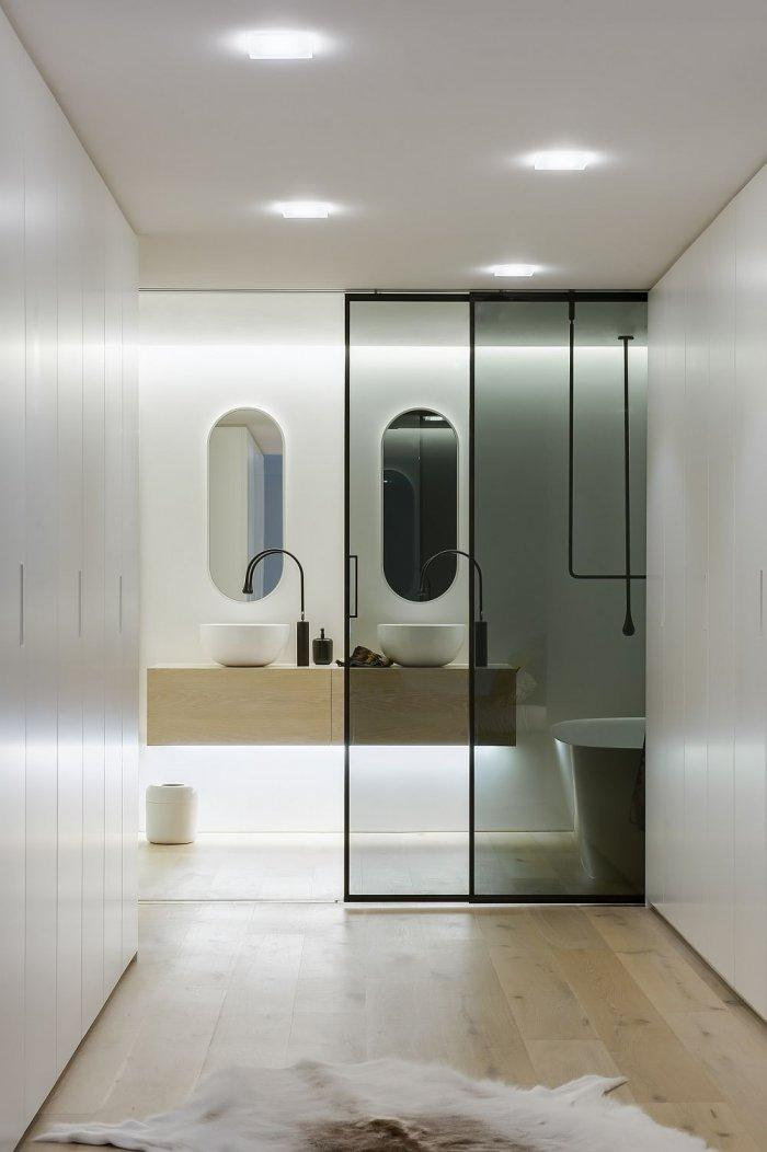 Contemporary bathroom in white with hallway and sliding door
