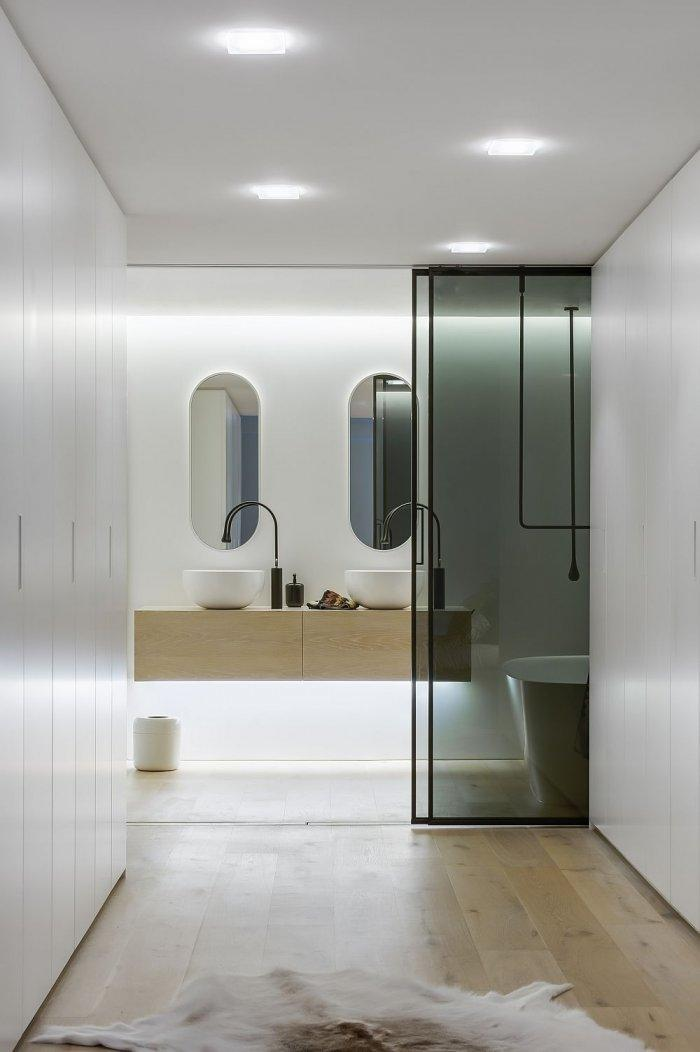 Contemporary bathroom in white with hallway leading to the main section