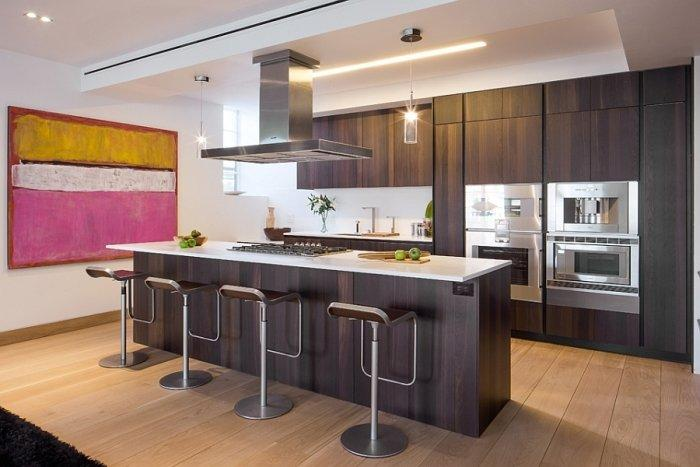 Contemporary penthouse kitchen with dark cabiners and long island