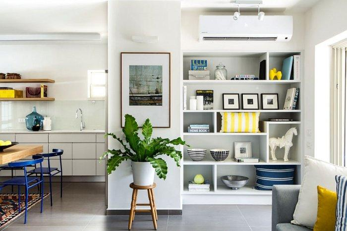 Eclectic corner with white shelves and abstract paiting on the wall