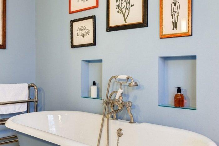 English bathroom design with colorful wall decorations and bluish walls