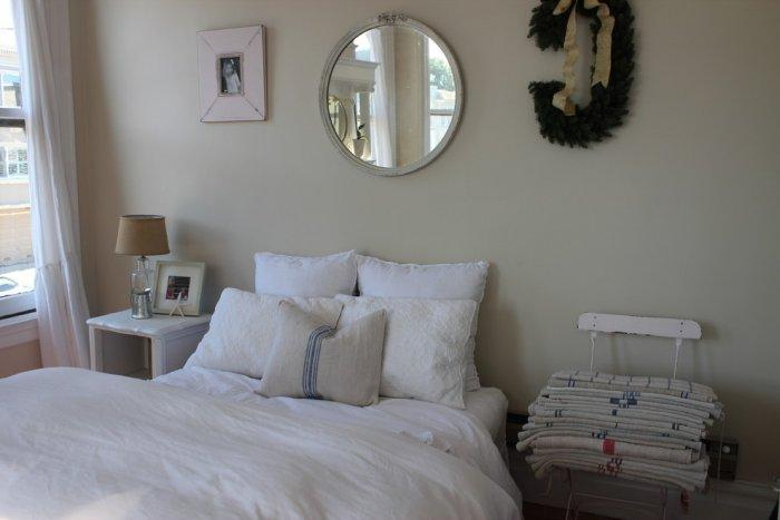 Farmhouse chic bedroom design with comfortable cozy bed and a lot of pillows