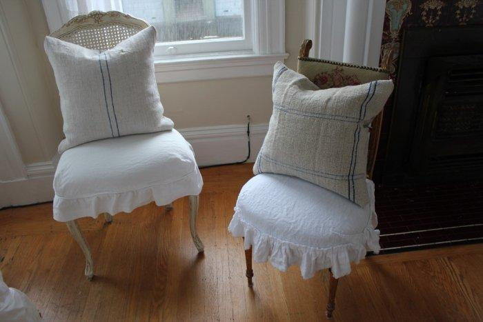 Farmhouse chic pillows decorate the two vintage chairs in the living room