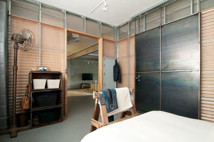 Industrial bedroom with vintage storage shelves and a fan