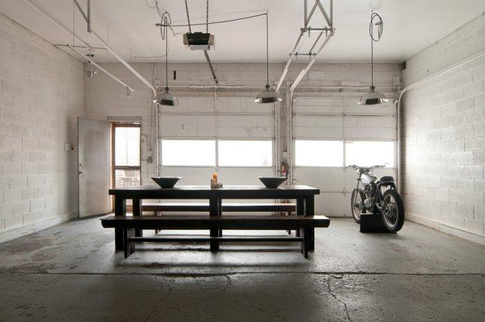 Industrial dining room with simple and raw design and concrete block wall