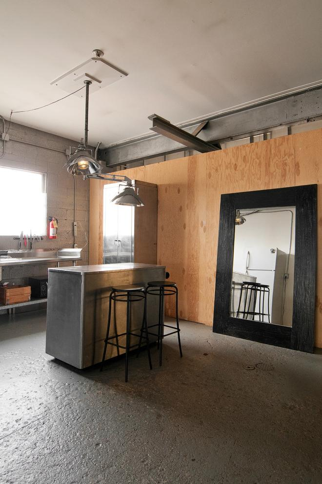 Industrial kitchen with small island and two bar stools