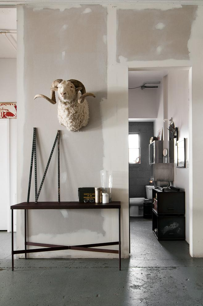 Industrial room leading to the bathroom with concerete floor