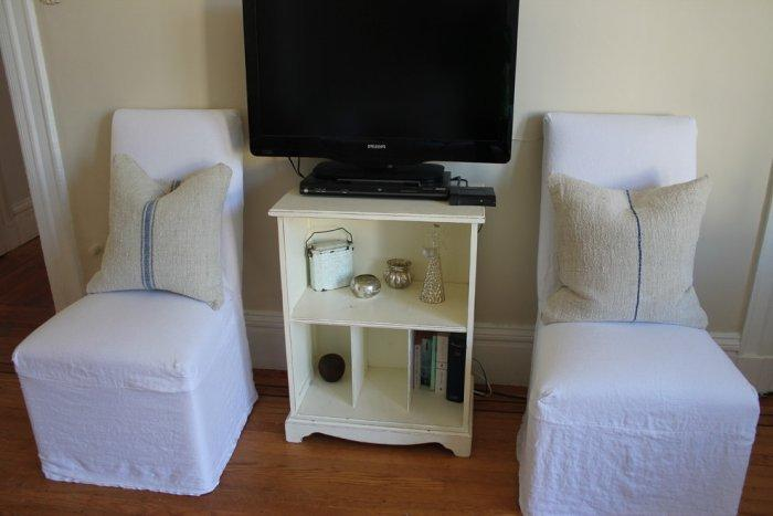 Living room with TV set and two chairs cover with white textile fabric